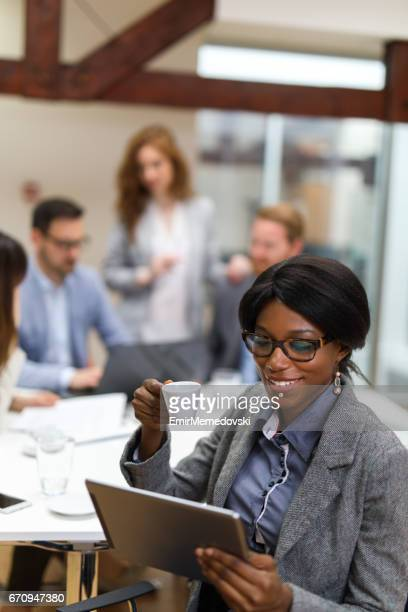 Young businesswoman using digital tablet and analyzing business report.