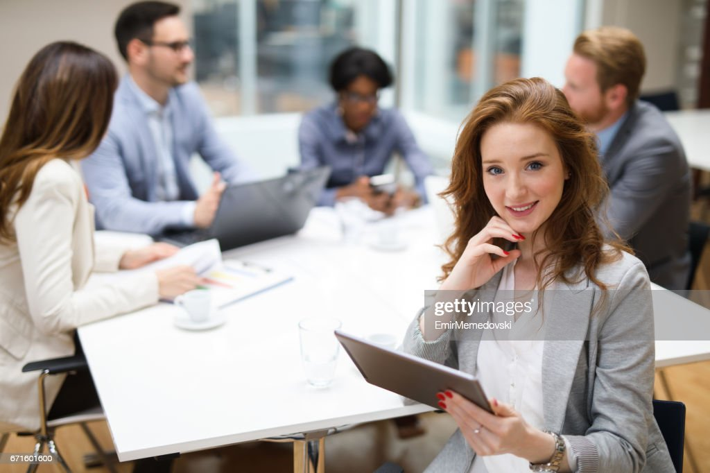 Young businesswoman using digital tablet and analyzing business report. : Stock Photo