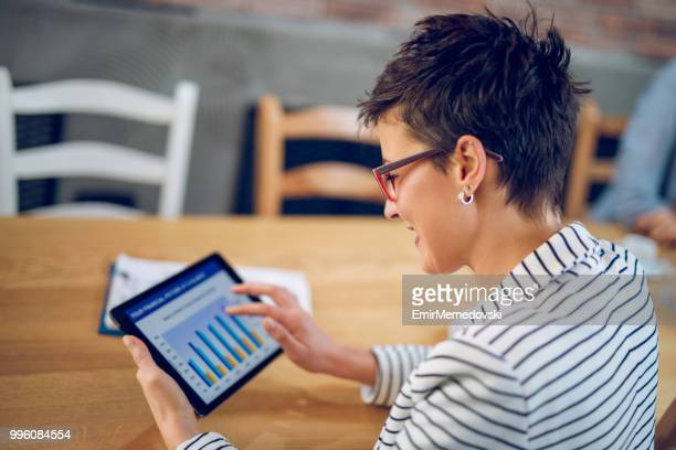 young businesswoman using digital tablet and analyzing business report - bar graph stock pictures, royalty-free photos & images