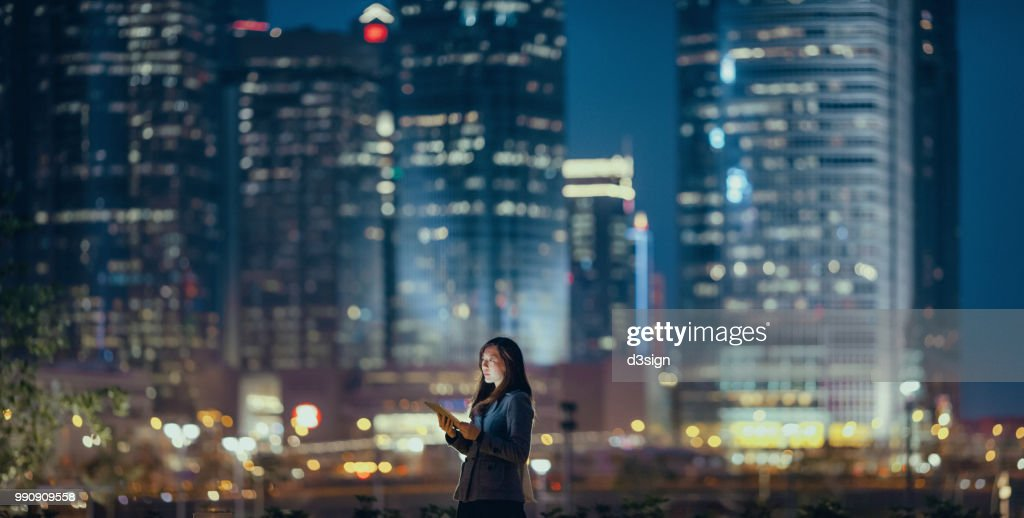 Young businesswoman using digital tablet in financial district, against illuminated corporate skyscrapers at night : Stock Photo