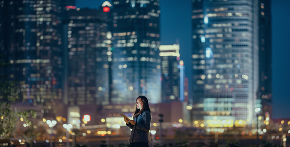 Young businesswoman using digital tablet in financial district, against illuminated corporate skyscrapers at night - gettyimageskorea