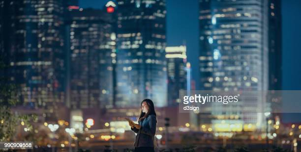 young businesswoman using digital tablet in financial district, against illuminated corporate skyscrapers at night - night stockfoto's en -beelden