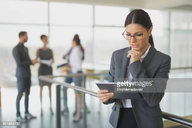Young businesswoman using digital tablet in office building hallway