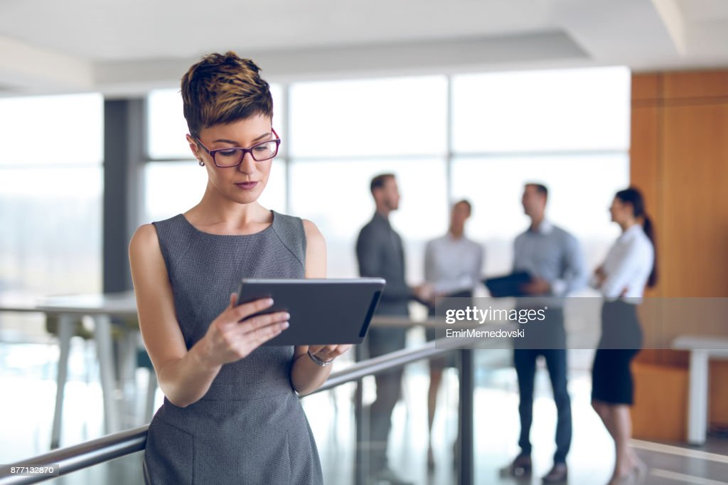 Young businesswoman using digital tablet in office building hallway. : Stock Photo