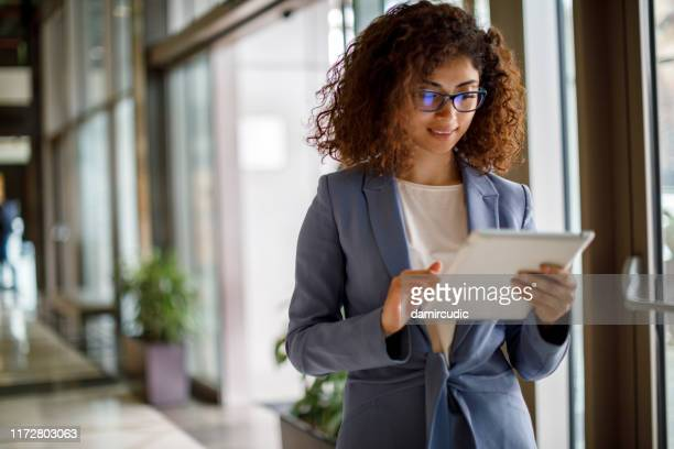 young businesswoman using digital tablet indoors - using digital tablet stock pictures, royalty-free photos & images
