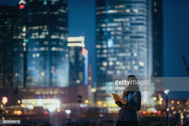 young businesswoman using digital tablet, looking back over illuminated city skyline with confidence at night - prosperity stock pictures, royalty-free photos & images