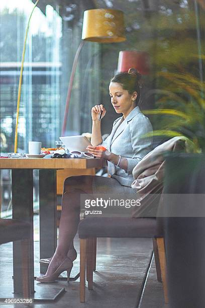 Joven mujer de negocios usando la tableta digital en el restaurante
