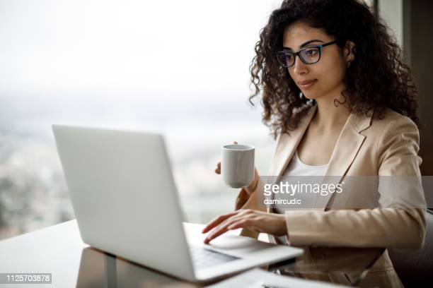 young businesswoman using laptop at a cafe - turkey middle east stock pictures, royalty-free photos & images