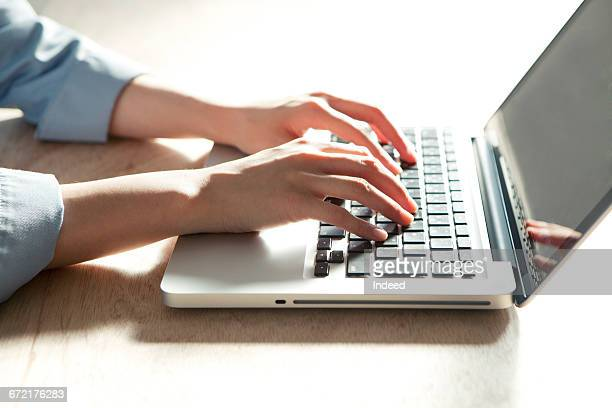 Young businesswoman using laptop at desk
