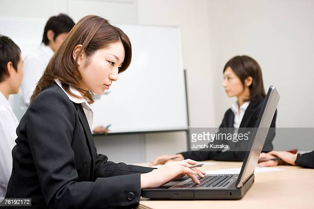 young businesswoman using laptop - 数人 ストックフォトと画像