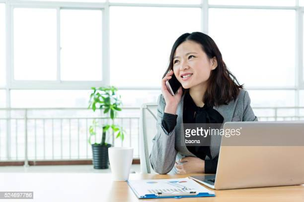 Young businesswoman using mobile phone and laptop
