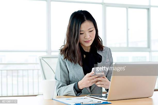 young businesswoman using mobile phone and laptop - sending stock photos and pictures