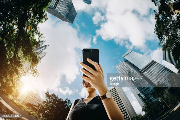 young businesswoman using mobile phone in city urban park against financial skyscrapers on a fresh bright morning - low angle view stock pictures, royalty-free photos & images