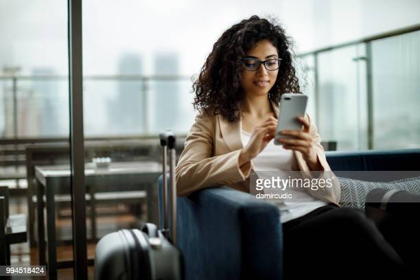 young businesswoman using mobile phone - arrival photos stock photos and pictures