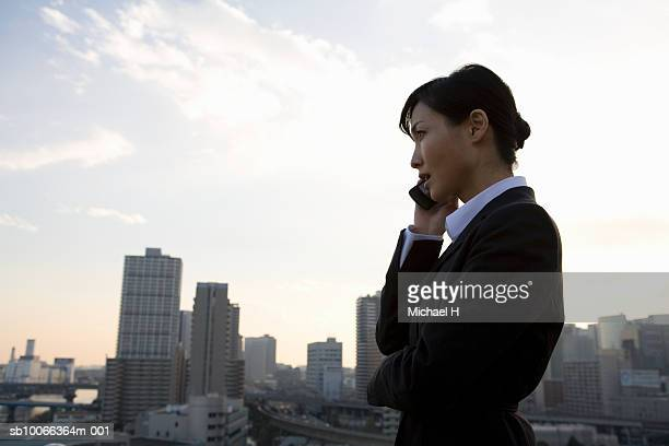 Young businesswoman using mobile phone, side view