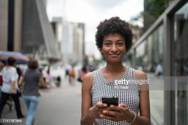 mulher de negócios nova que usa o retrato móvel na cidade - trabalhadora de colarinho branco - fotografias e filmes do acervo