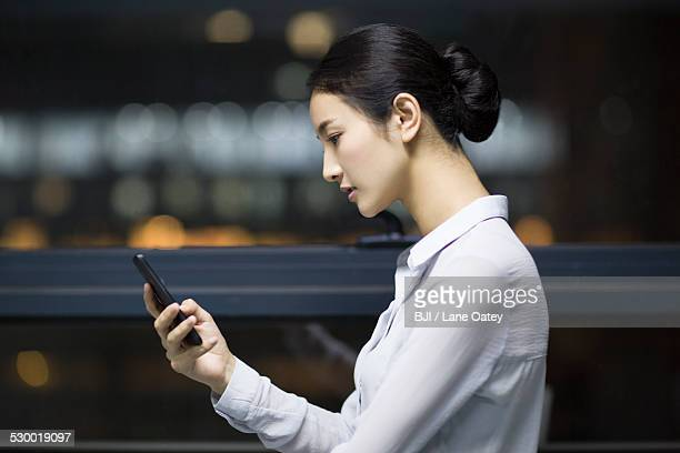 Young businesswoman using smart phone in office