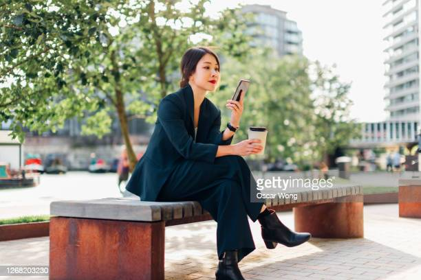 young businesswoman using smart phone on bench at park, with coffee cup on hand - asian and indian ethnicities stock pictures, royalty-free photos & images
