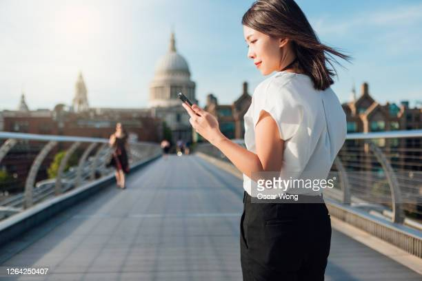 young businesswoman using smart phone on footbridge in the city - space mission stock pictures, royalty-free photos & images
