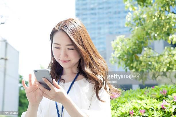 young businesswoman using smart phone - japanese ol ストックフォトと画像