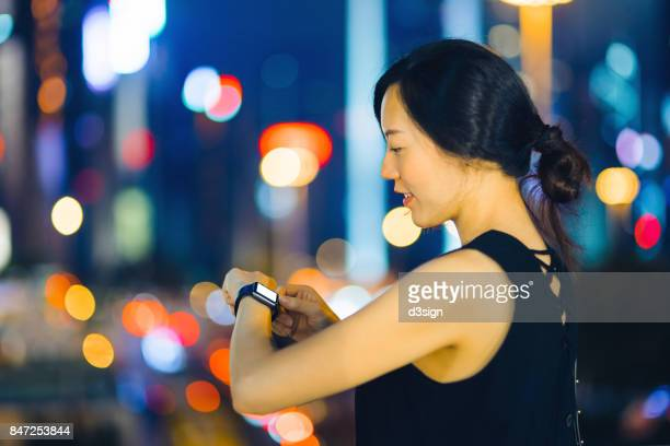 Young businesswoman using smart watch at night, with illuminated and colourful city street lights behind as background