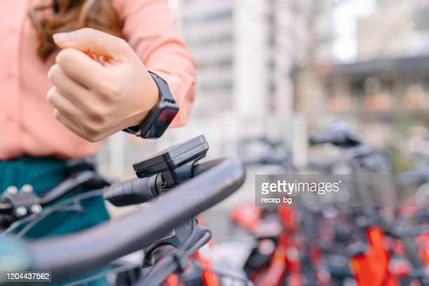 スマートウォッチを使用して自転車を借りる若いビジネスウーマン - スマートシティ ストックフォトと画像