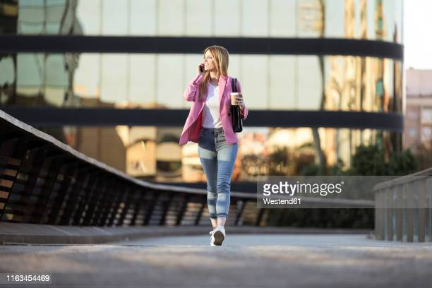 young businesswoman using smartphone and holding coffee to go - 歩道橋 ストックフォトと画像