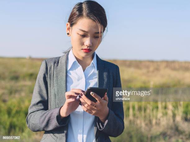 young businesswoman using smartphone at country road