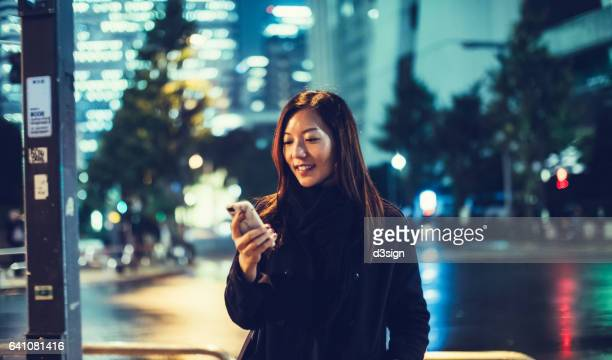 Young businesswoman using smartphone in downtown financial district at night.