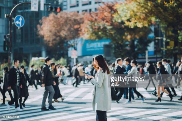 young businesswoman using smartphone on city street against busy commuters and corporate buildings in tokyo, japan - japan commuters ストックフォトと画像