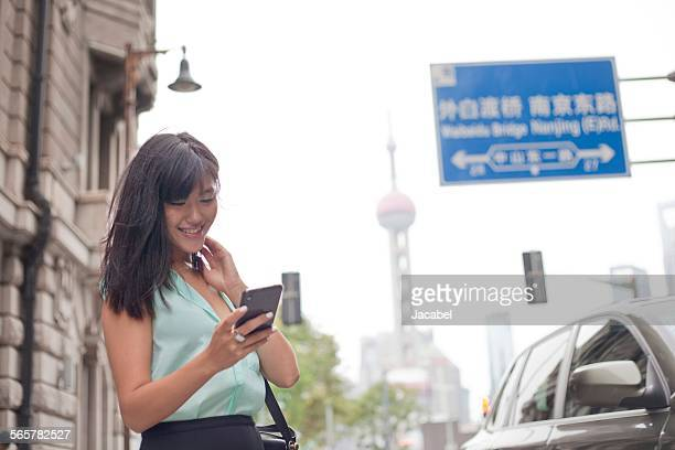 Young businesswoman, using smartphone, outdoors, Shanghai, China