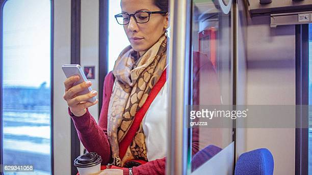 Young businesswoman using smartphone while commuting to work by train