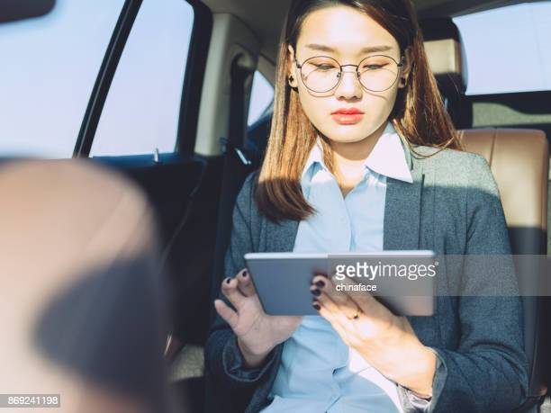 young businesswoman using tablet on car backseat