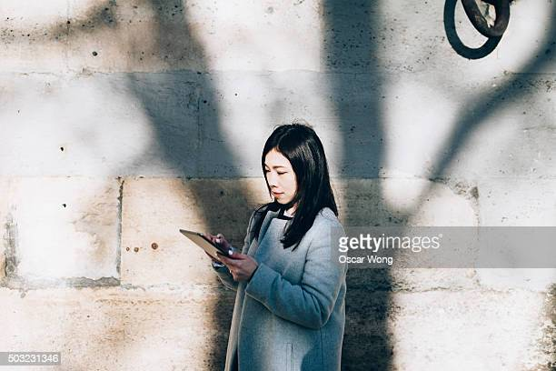 Young businesswoman using tablet outdoors