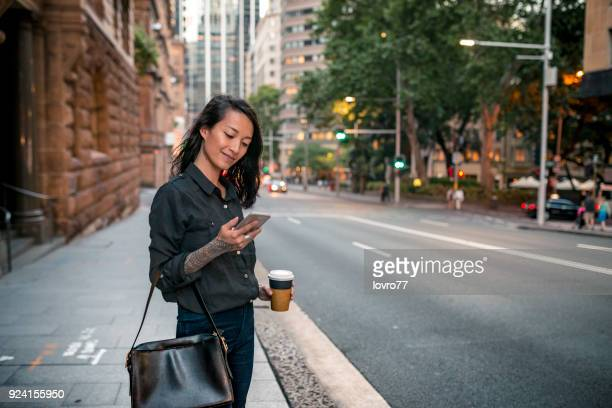 young businesswoman waiting for taxi in sydney - mobile phone stock pictures, royalty-free photos & images