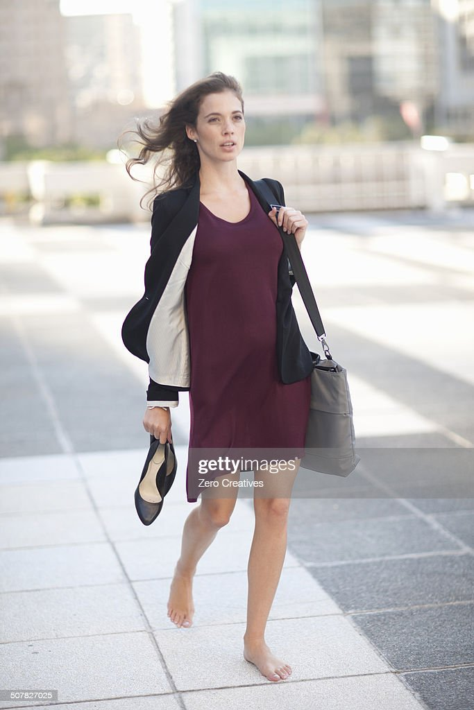 Young businesswoman walking barefoot and carrying high heels : Stock-Foto