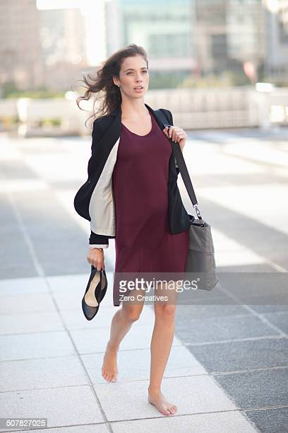 Young businesswoman walking barefoot and carrying high heels