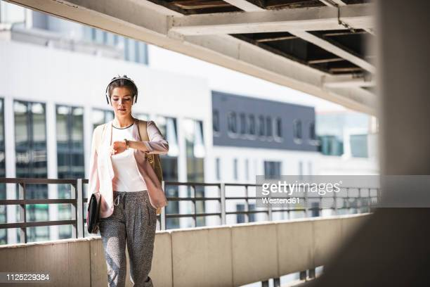 young businesswoman walking in parking garage, checking time - dringendheid stockfoto's en -beelden