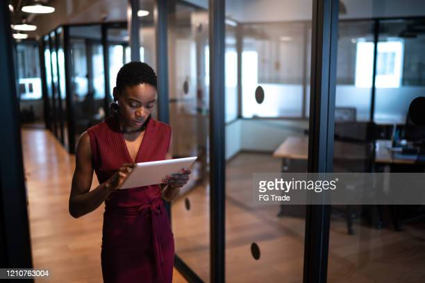 young businesswoman walking with digital tablet at coworking - corporate business stock pictures, royalty-free photos & images