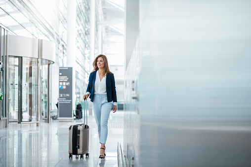 Young businesswoman walking with luggage at the airport - gettyimageskorea