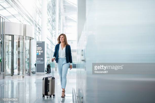 young businesswoman walking with luggage at the airport - luchthaven stockfoto's en -beelden