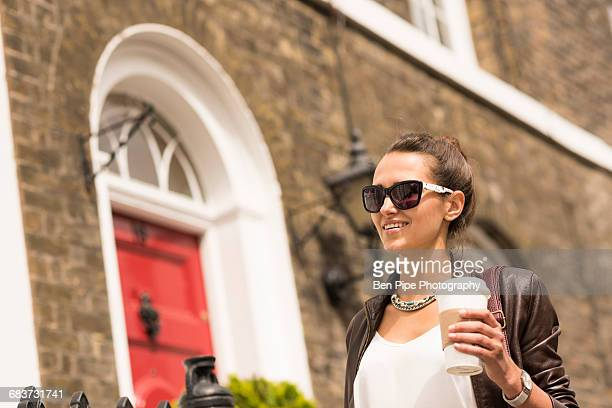 Young businesswoman walking with takeaway coffee on city street, London, UK