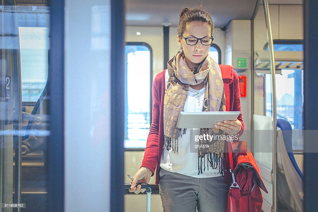 Young businesswoman watching tablet while commuting to work by train : Stock Photo