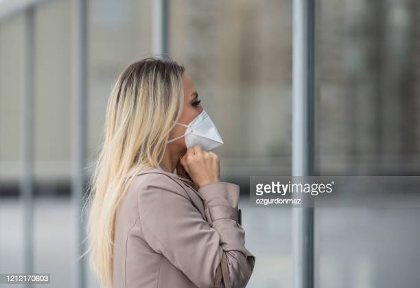 young businesswoman wearing a protective face mask - n95 respirator mask stock pictures, royalty-free photos & images