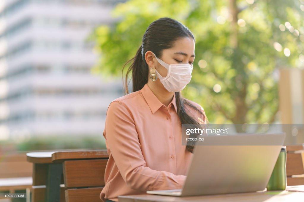 市内でフェイスマスクを着用した若いビジネスウーマン : ストックフォト