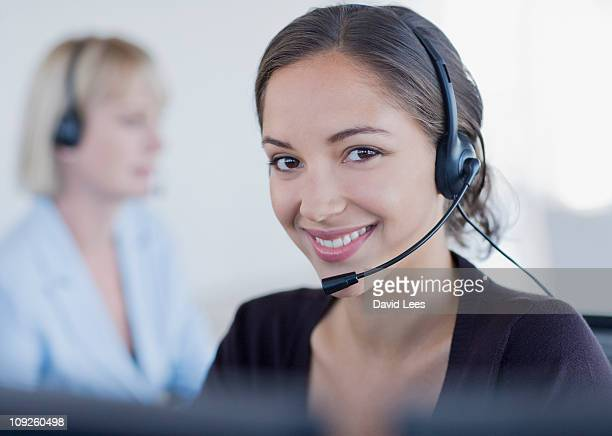 Young businesswoman wearing headset, smiling