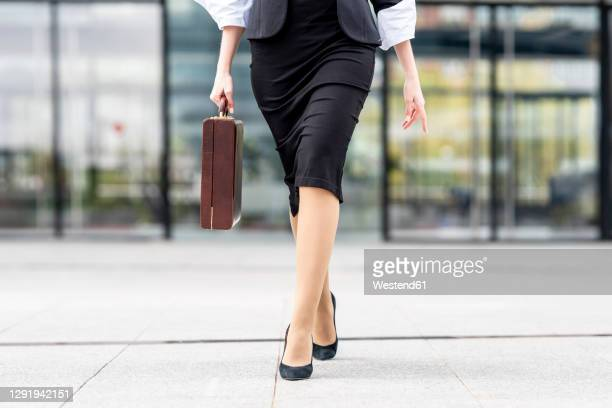 young businesswoman wearing high heels walking with briefcase on footpath - low section stock pictures, royalty-free photos & images