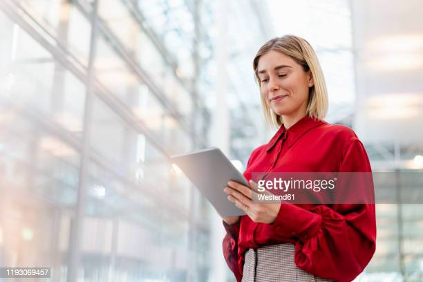 young businesswoman wearing red shirt using tablet - red shirt stock pictures, royalty-free photos & images