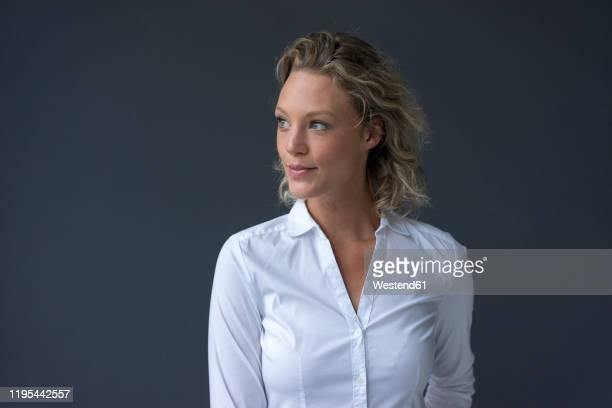 young businesswoman wearing white shirt looking sideways - 白いシャツ ストックフォトと画像