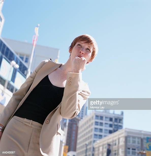 Young businesswoman whistling for taxi on city street
